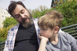 Vater und Sohn auf Parkbank in Wohnsiedlung. Berlin, Deutschland.